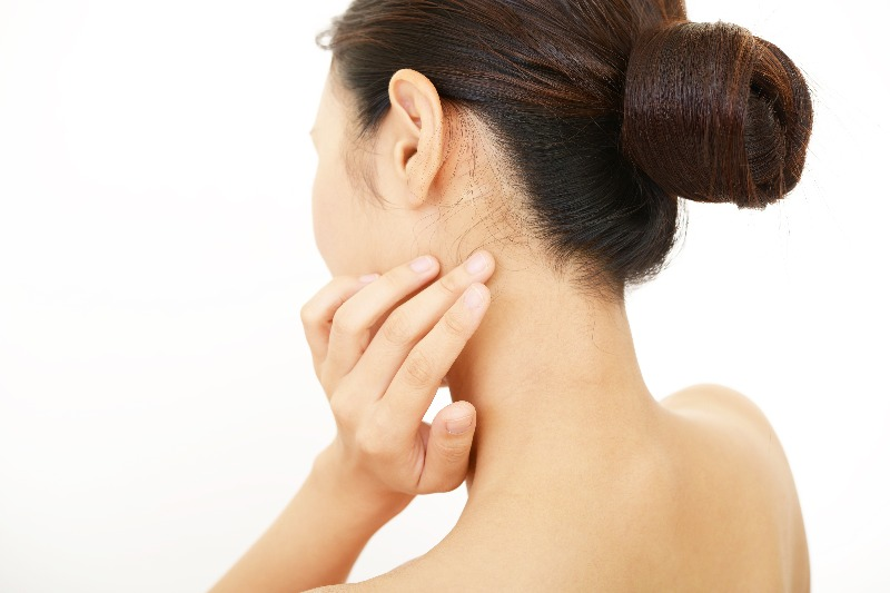 Woman touching skin tag on her neck